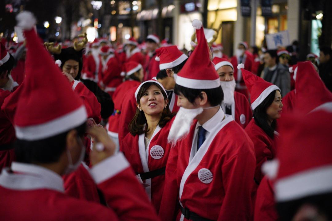 2017年12月22日,日本首都東京,近200名穿上聖誕老人服的員工在丸之內地區的街道上巡遊。