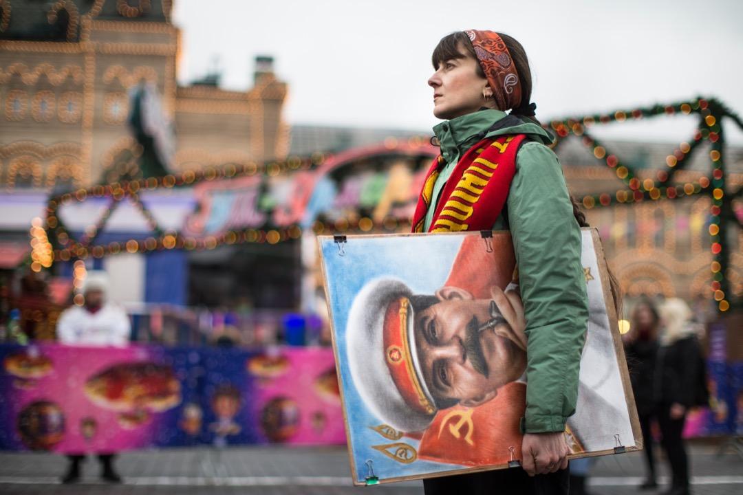 2017年12月21日,俄羅斯首都莫斯科,一位藝術家手持前蘇聯領導人史太林的肖像,站在正舉行聖誕和新年慶祝活動的紅場前。