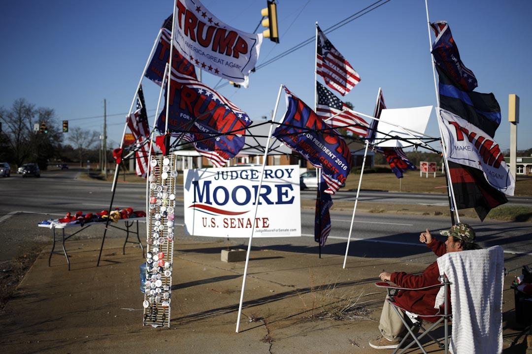 特朗普一直對是否支持穆爾半心半意,直到[12月4日才打電話,給穆爾表示自己全力支持。圖為印有特朗普名字的旗幟混合在穆爾的競選宣傳上。