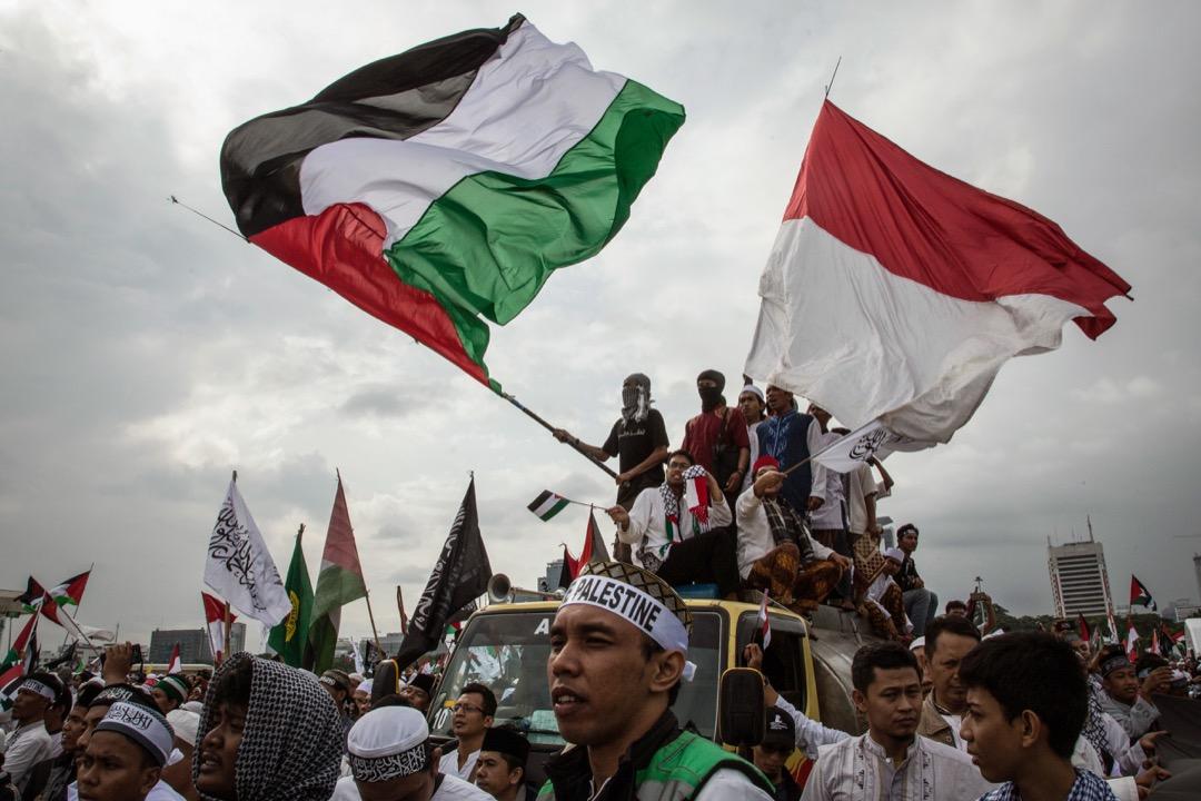 2017年12月17日,印尼首都雅加達,民眾揮舞巴勒斯坦和印尼國旗,反對美國承認耶路撒冷成為以色列首都的決定。當地警方估計約有八萬示威者要求抵制美國和以色列的企業。