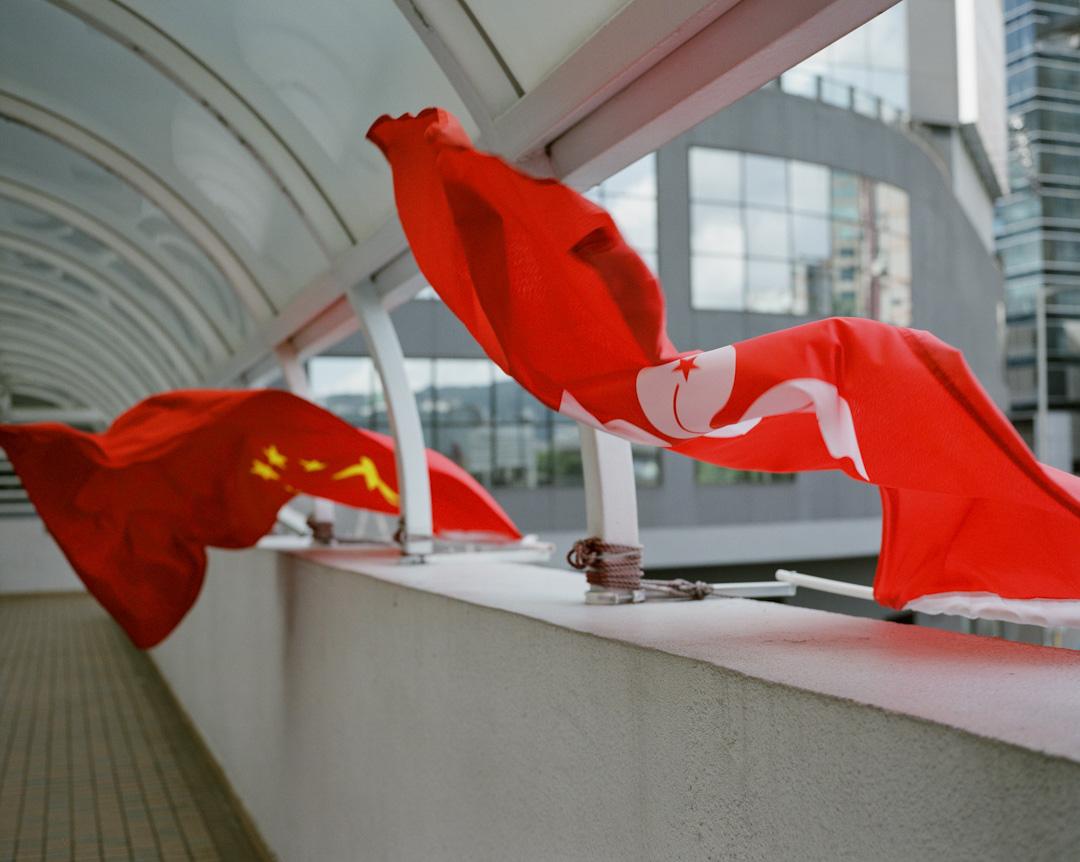 2017年6月,觀塘一條天橋上,有中國的五星紅旗及香港特區區旗隨風飄揚。