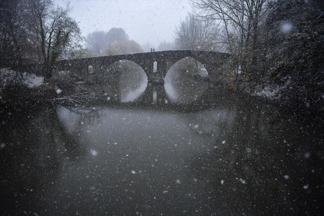 2017年12月1日,西班牙東部城市潘普洛納,有路人在大雪中走過阿爾加河馬格達萊納橋。
