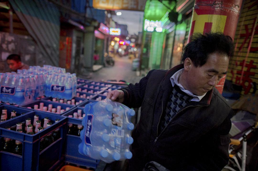 「低端人口」的污名或驅逐行動的無情,某程度上都已宣告了「城市夢」的破滅。一名男子在北京黑池村為一家商店運送瓶水和啤酒。 攝:Nicolas Asfour/AFP/Getty Images