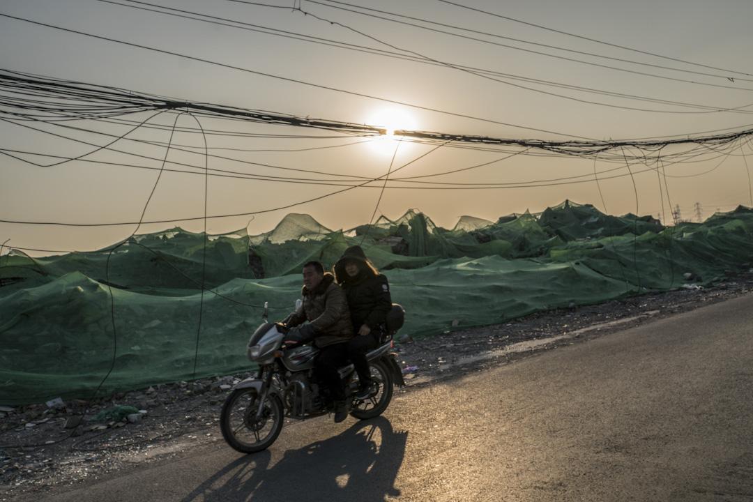 黃昏時分,有居民乘著摩托車經過北京朝陽區一條被化成瓦礫的村莊。 攝:Stanley Leung/端傳媒