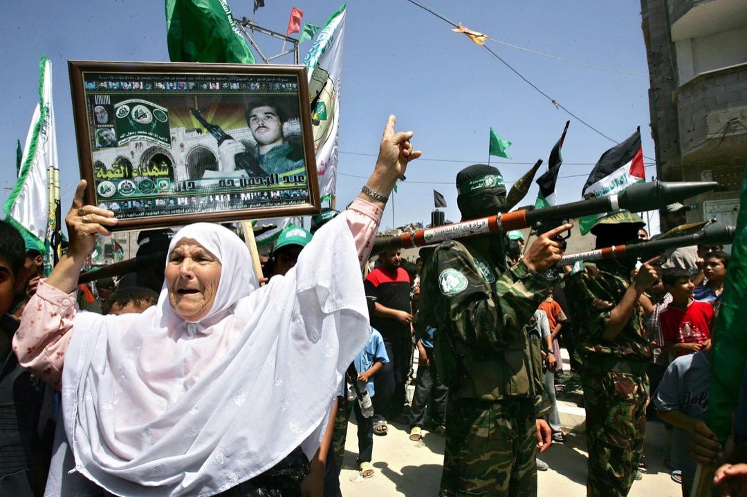 一名巴勒斯坦婦人在極端組織哈馬斯的戰士前那著橫額手舞足蹈,慶祝以色列軍隊撤出加沙。