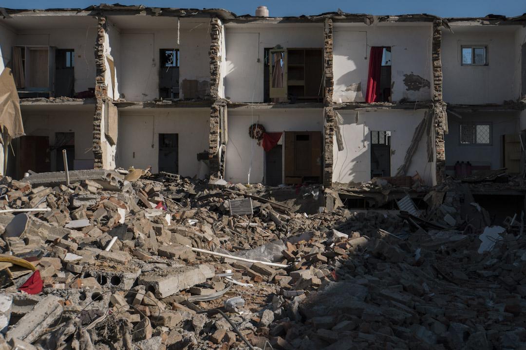 一棟公寓還沒完全倒下,可見到公寓裏的房間還剩下一些住客遺下的傢俱和裝飾。 攝:Stanley Leung/端傳媒