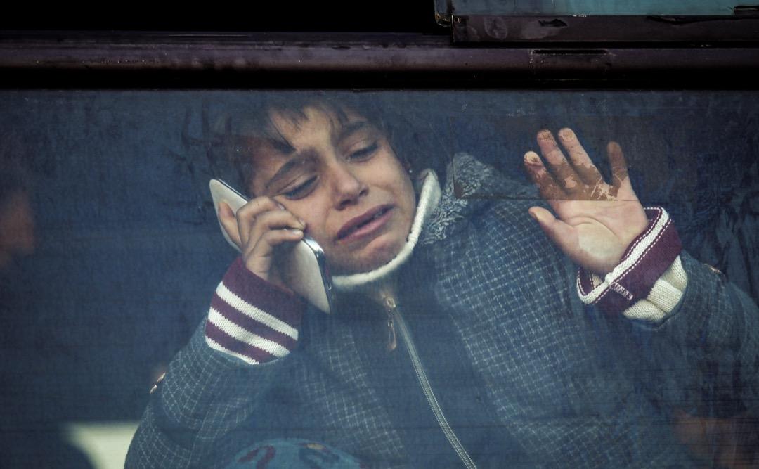 2017年12月16日,加沙地帶,一名男孩在經過拉法關口前往埃及之前,在公交車上將電話放在耳邊,向窗外揮手告別。