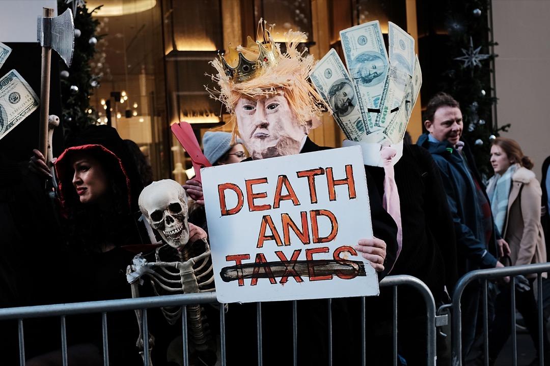 這些優勢行業高度集中在美國幾大城市,要想進一步「涓滴」到其他中下層工人,他們需向工作機會多、勞工稀缺地區遷徙移民。可惜規劃方式讓住房供給極難增加,形成有工作的地方住不起,住得起的地方沒工作的窘境。圖為示威者到紐約市特朗普大廈抗議特朗普的稅改方案。