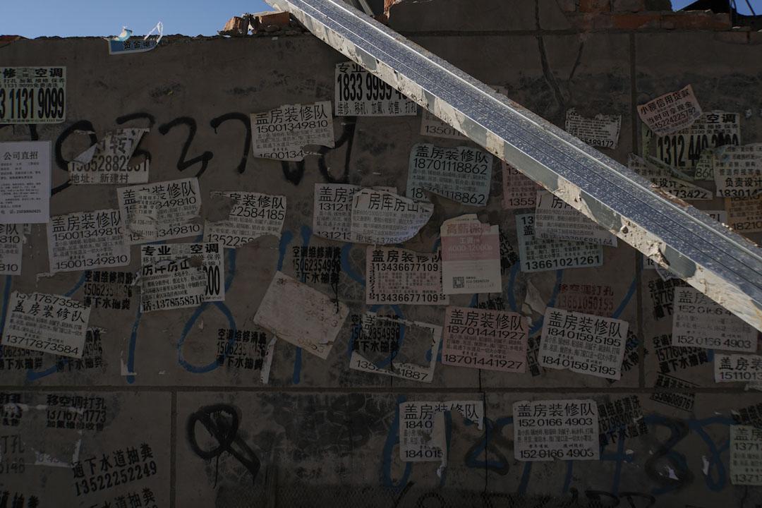 還沒倒下的建築物牆壁上,貼滿蓋房子和裝修的廣告。