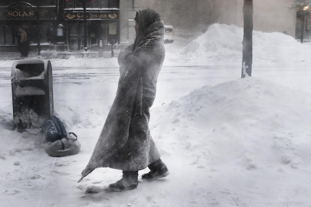 2018年1月4日,美國馬薩諸塞州城市波士頓受寒流侵襲,下暴風雪,一名無家者在一家咖啡店外徘徊。