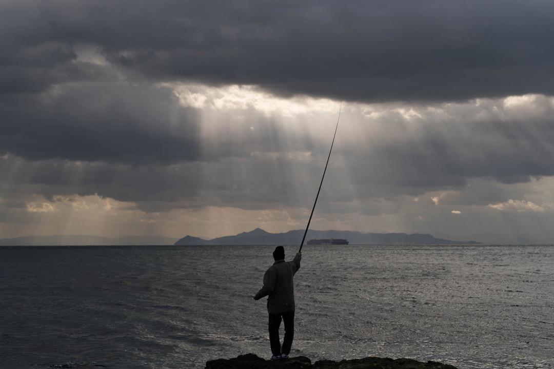 2018年1月24日,一名男子在希臘雅典的海邊釣魚。