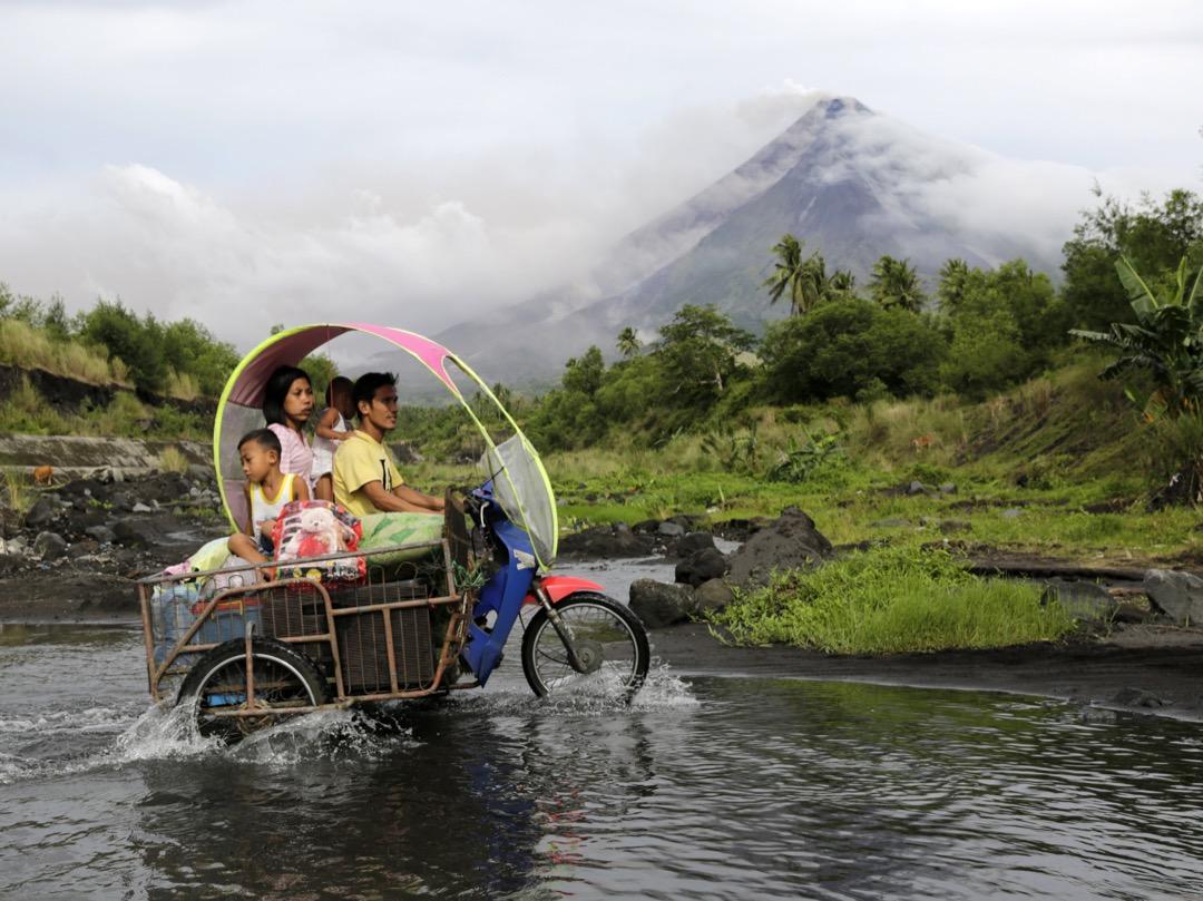 2018年1月16日,菲律賓城市黎牙實比,村民帶著隨身物品坐摩托車經過馬榮火山。近日火山不斷湧出火山灰,有爆發危機,菲律賓當局在1月15日提高警戒級別,周邊居民需疏散。