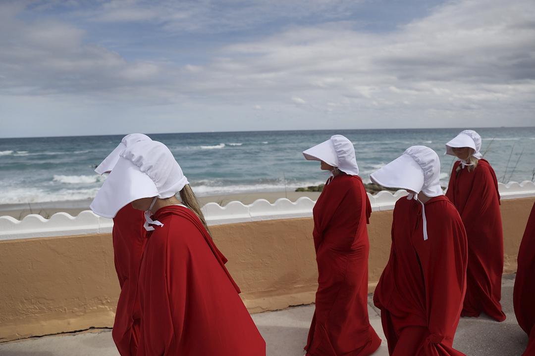 佛羅里達州棕櫚灘,有示威者穿上電視劇《使女的故事》中的使女的服飾,遊行至特朗普於佛羅里達州的別墅馬阿拉歌(Mar-a-Lago),諷刺在他管治下,美國變得像劇中的威權國度。 攝:Joe Raedle/Getty Images
