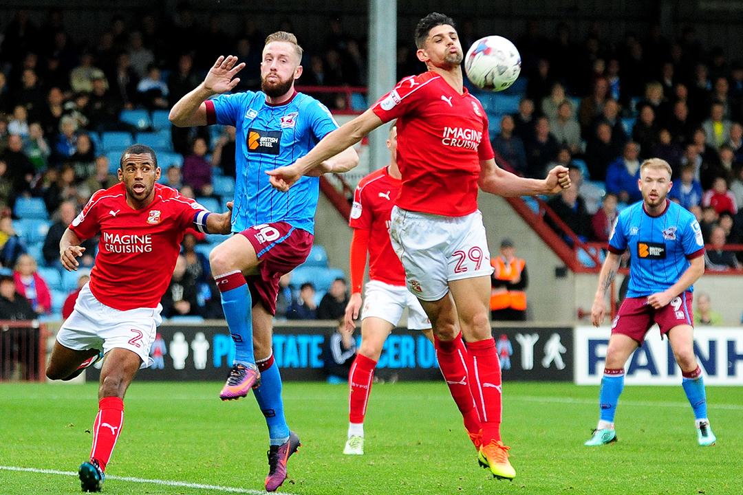 2016年10月29日,英國球會史雲頓(Swindon Town F.C.,著紅色球衣)客場對陣斯肯索普(Scunthorpe United F.C.,著藍色球衣)。