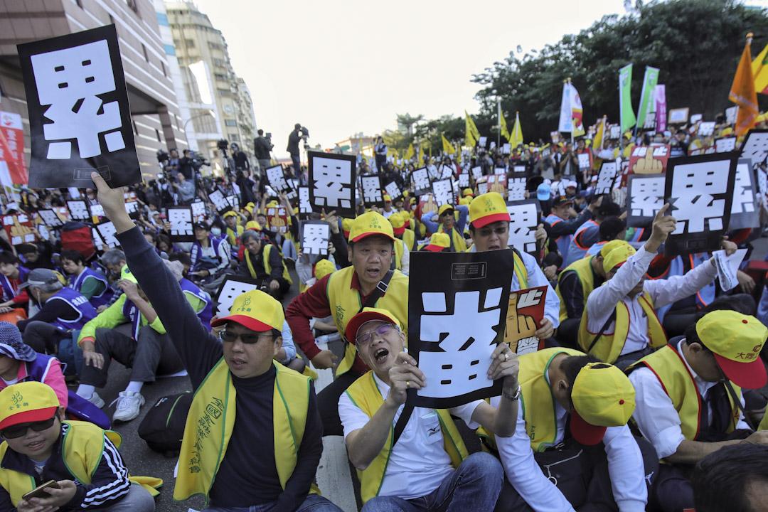 2017年12月23日,「反勞基法修惡大遊行」,示威人士集結於民進黨中央黨部前地出發,主辦單位估有逾1萬人參加,群眾高舉手中「終止過勞」、「累」標語發出怒吼。 攝:張國耀/端傳媒