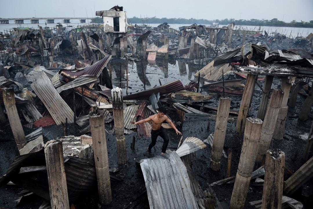 2018年1月24日,菲律賓甲米地省巴科奧爾鎮,一場火災燒毀了岸邊約200多所房屋,約1000多名居民受影響,火災沒造成傷亡。一名當地居民在災區裏的一塊鐵皮屋頂上走過。