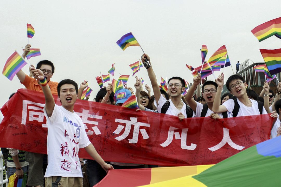 2013年5月17日,中國湖南長沙舉行的同性戀反歧視遊行,年輕人舉著彩虹旗呼籲大眾對同性戀的理解。 攝:STR/AFP/Getty Images