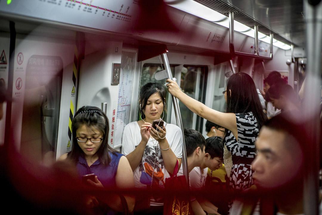 微信月活躍用戶趨向10億量級,已接近全社會階層的複雜度。圖為廣州地鐵上,大多數乘客都觀看手機。