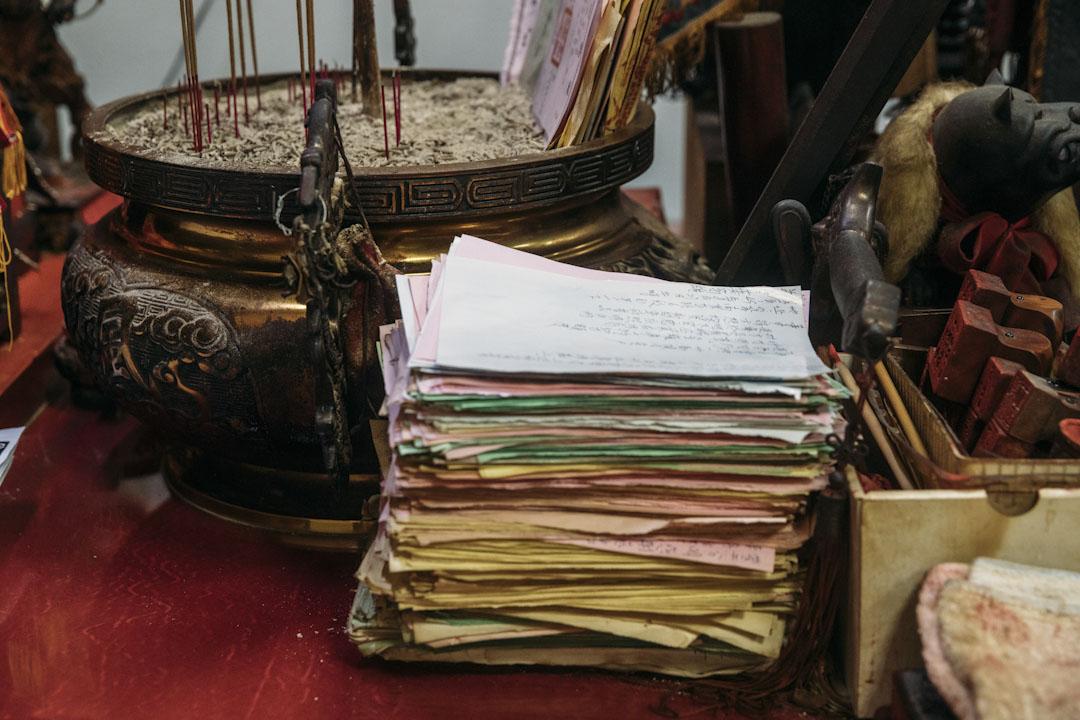 板橋玉旨代天堂所供奉的王爺案前,是ㄧ疊厚厚的信徒問事紀錄。調查局去年底搜索代天堂,也帶走了部分信徒的問事單。
