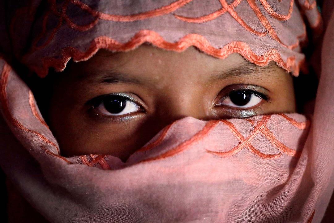 八月下旬,十名士兵闖進R的家,將她兩個弟弟拖到外面,綁在樹上毆打。R嘗試逃走,但被抓著。士兵同樣把她綁在樹上,扯掉她的首飾,也扯掉她的衣服,然後把她輪姦。難以忍受的痛令她昏過去了。她的哥哥回家後看到後,立刻把她帶到緬孟邊境,到孟加拉後,當地醫生隨即給她吃避孕藥。R非常念掛弟弟們,晚上亦經常被惡夢纏繞。R輕聲地說:我被強姦前,很漂亮。