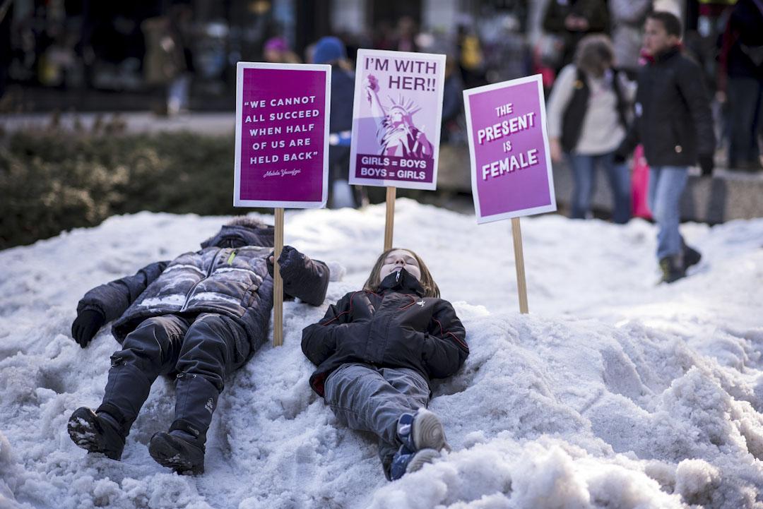 芝加哥,兩位參與2018年度女性大遊行的年輕人遊行期間躺在雪地稍作休息。