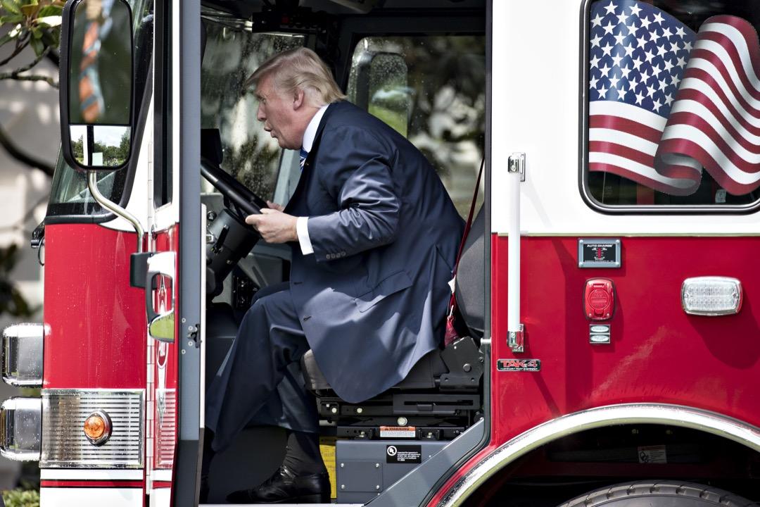 美國總統特朗普政府在過去一年,其實都在穩定地推進他在競選和就職演說時承諾的經濟民族主義政策。圖為2017年7月17日,特朗普在白宮草坪啟動表揚美國工業的「美國製造週」,期間他坐上一輛美國製造的消防車。 攝:Andrew Harrer/Bloomberg via Getty Images