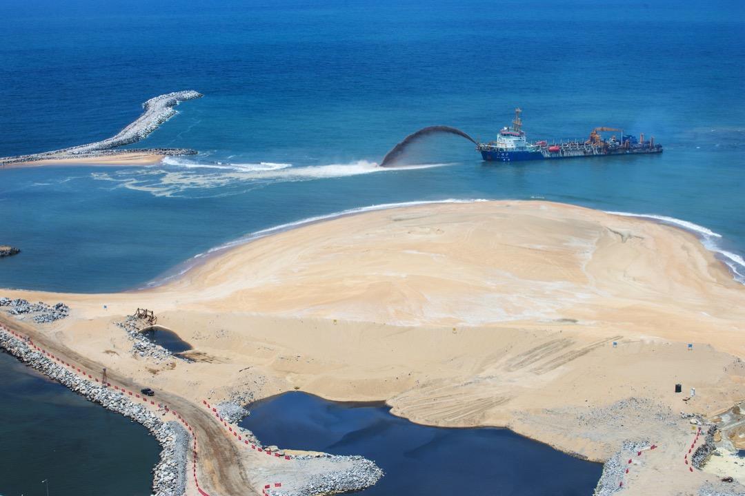 中方從廣州調來了大型噴砂船「萬頃沙」號在內的三艘船,日夜不停地往工地填沙,港口城目前還在填沙的階段,已經完成了61%。