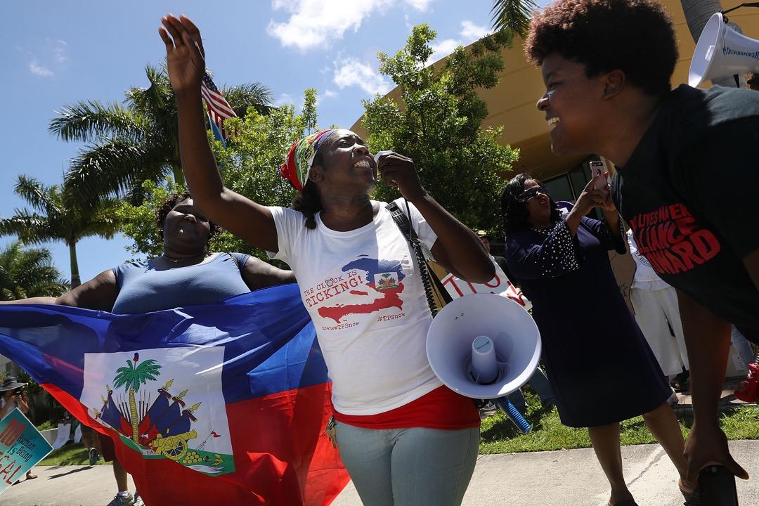 2017年底,白宮宣布其計劃停止46,000名海地居民在美國的受保護身份(Temporary Protected Status)。圖為同年5月,居住在佛羅里達州的海地居民到街頭示威,要求特朗普政府不要終止給予海地居民在美國的受保護身份的計劃。