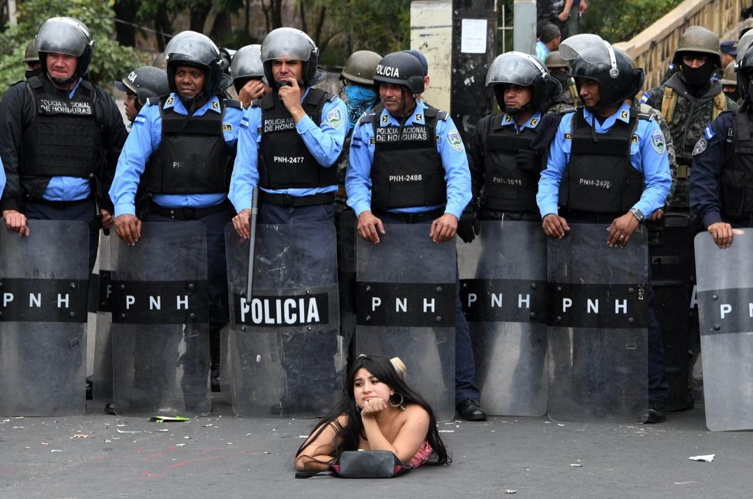 2018年1月21日,洪都拉斯首都特古西加爾巴,有民眾參與示威,抗議總統埃爾南德斯在大選中勝出連任,一名「反對獨裁聯盟」總統候選人 Salvador Nasralla 的支持者趴在拿著盾牌的警察前。