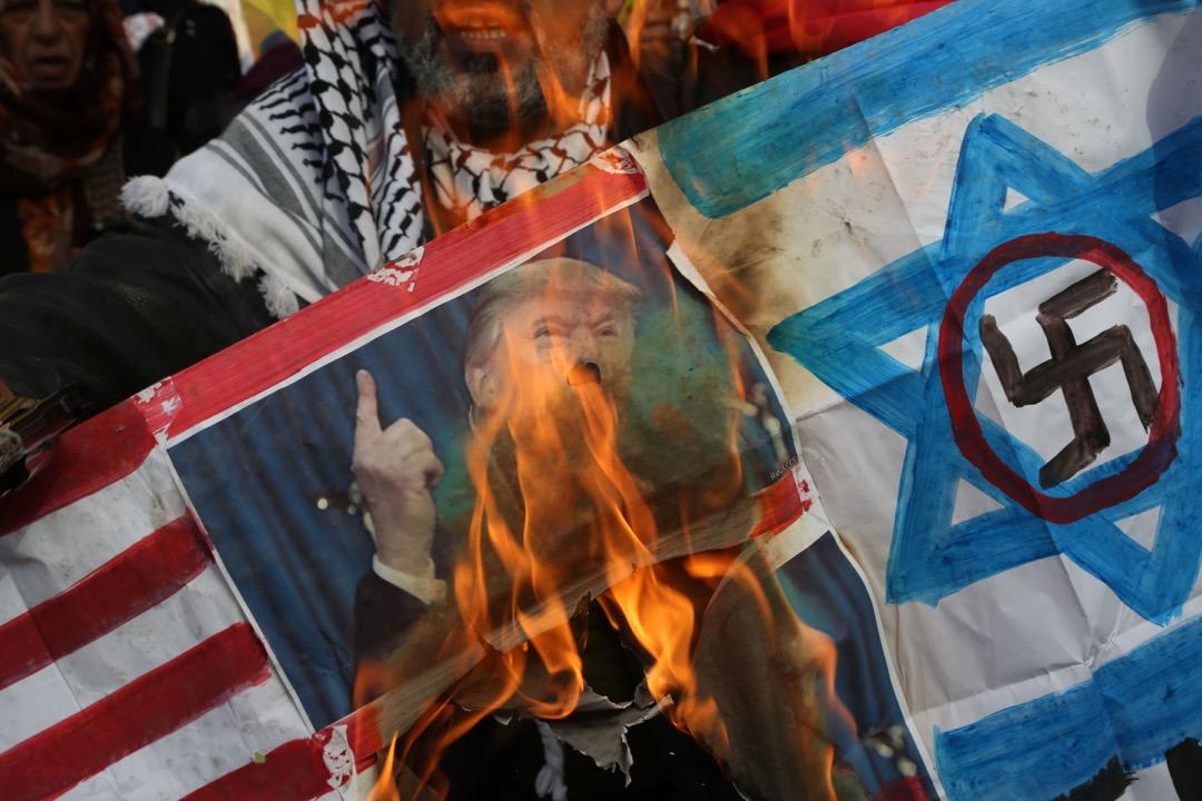 經過一輪交鋒,中東形成了俄羅斯、敘利亞、伊朗與什葉派武裝組織對抗以色列、沙特及海灣國家、遜尼派武裝組織與美國的明確列陣。圖為一名巴勒斯坦人在特朗普承認耶路撒冷為以色列首都後焚燒特朗普肖像抗議。