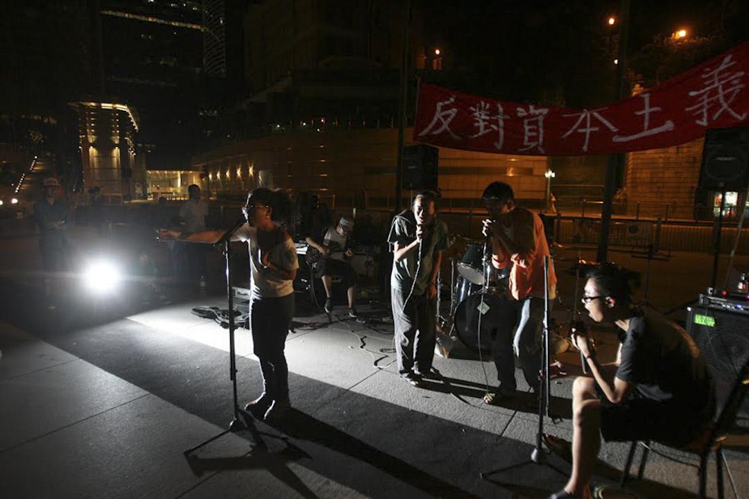 2011年的秋天,香港一批社運青年響應佔領華爾街運動,佔領中環的匯豐總行地面廣場,撐起帳蓬,組織物資進場,準備長期留守;橫額上有剛勁筆跡寫著「打倒資本主義」。