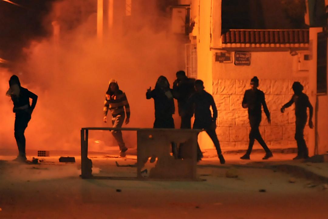 2018年1月10日,突尼西亞抗議者向安全部隊投擲石塊,安全部隊發射催淚瓦斯。 攝:Sofiene Hamdaoui/Getty Images