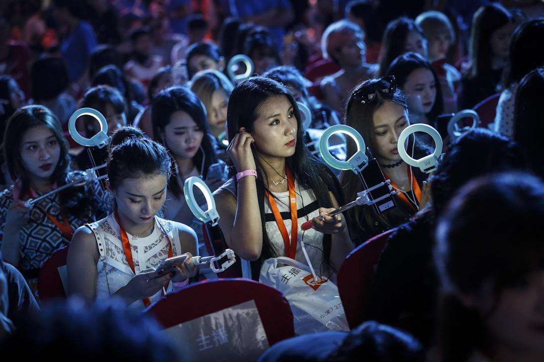 直播的觀看人數注水嚴重,目前為止,沒有一家直播直播的數據監測向公眾開放。圖為2016年7月27日,北京的網紅手持手機和環形自拍燈在現場直播發布會。