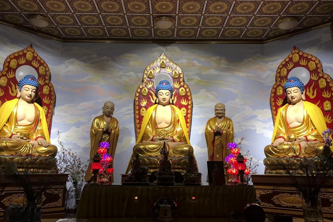 四方四正的佛堂約一百多平米,正中擺着三尊佛像——釋迦牟尼、阿彌陀佛和藥師佛——每尊佛像旁邊,都有兩位菩薩的立像,是大雄寶殿常見的式樣。