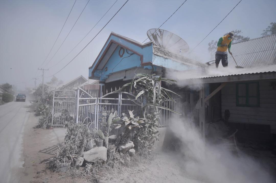 2018年2月20日,印尼北蘇門塔納省卡羅市,Sinabung 火山早前爆發,一名當地居民正清理屋頂上的火山灰。