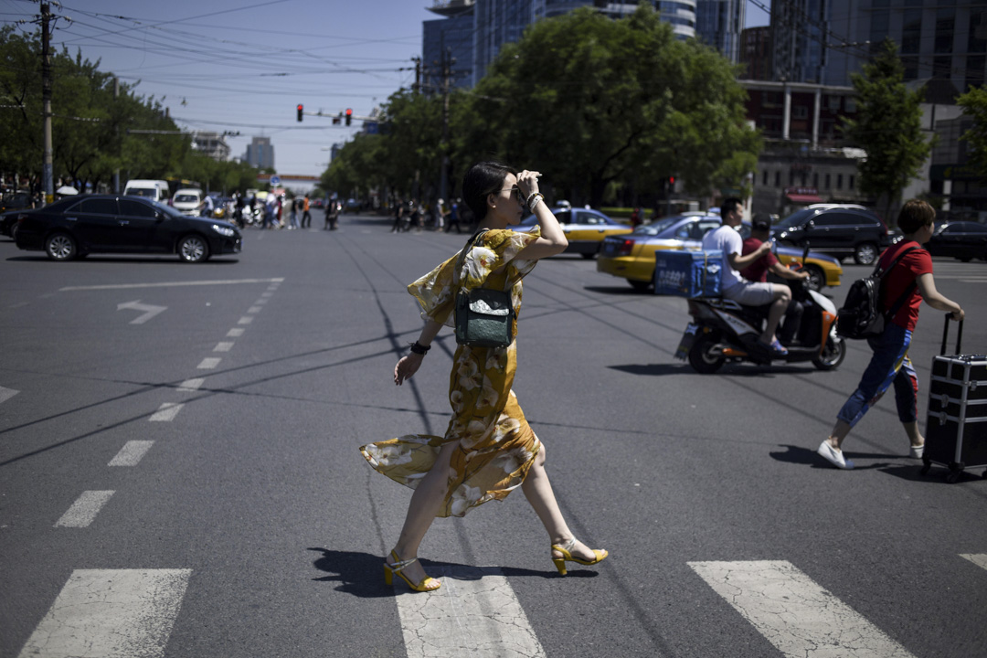 作為一個女權主義的運動者,覺得就是永遠要去把那一些隱藏的社會問題揭露出來,永遠不會滿意。  圖為北京一名女士正在過馬路。 攝:Wang Zhao/AFP/Getty Images