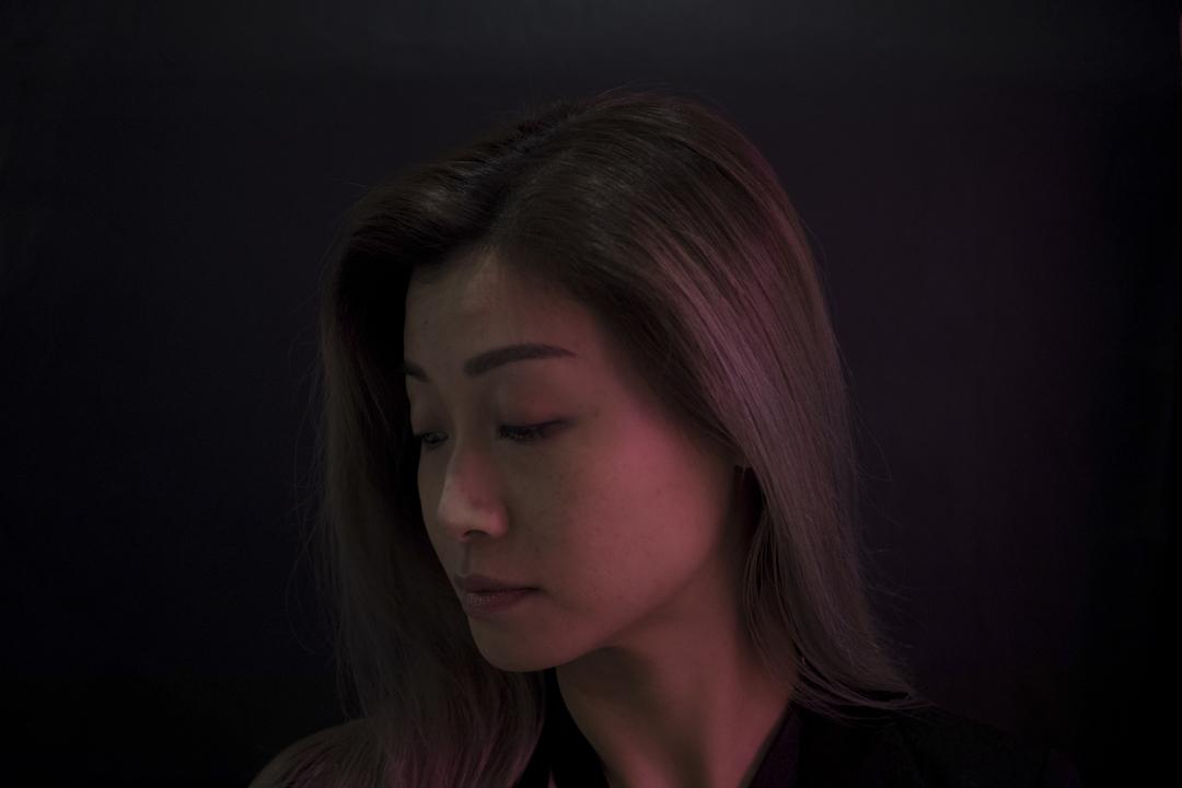 Candy在粉紅色的光管映照下,細說那段長達十年的婚姻裡一直過著守寡一般的無性生活,讓她的生活乾涸不堪。 攝:Stanley Leung/端傳媒