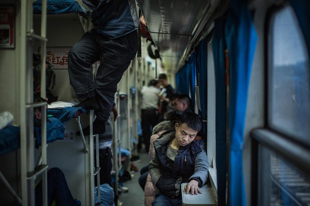 硬臥的乘客,睡眼惺忪坐在窗邊。
