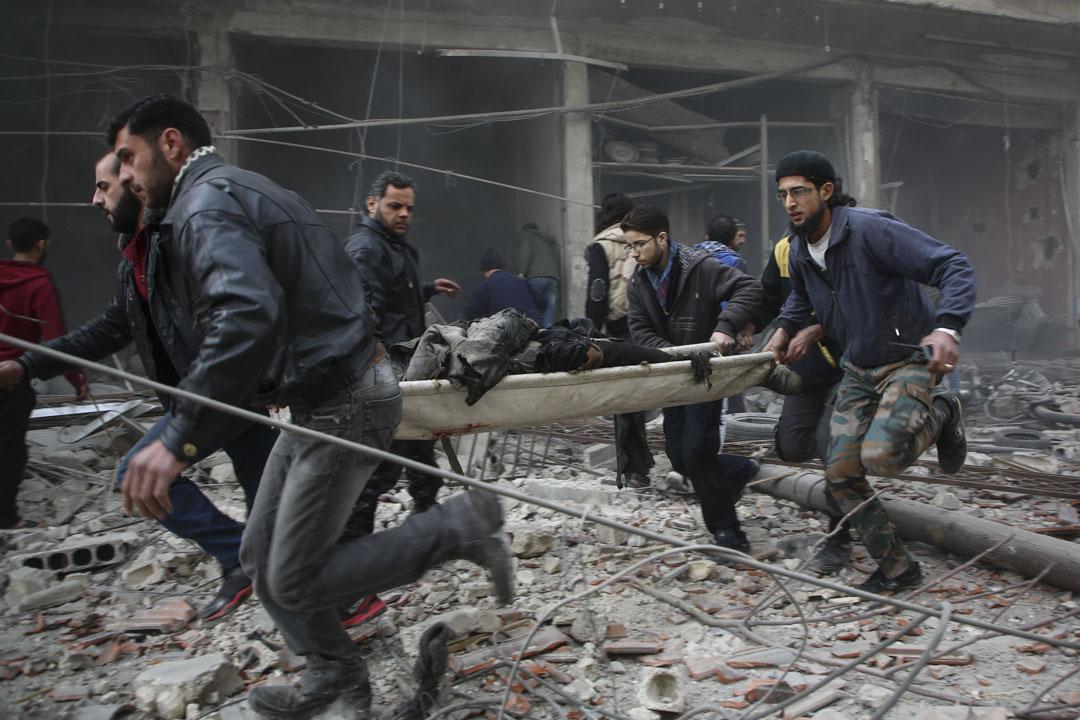 2018年2月6日,敘利亞首都大馬士革城東的巴卜圖馬區遭反政府武裝炮擊,至少5名平民喪生。圖為敘利亞救援人員聯合抬走傷者。