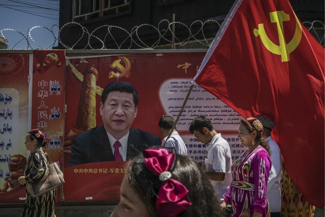 2017年6月30日,新疆喀什,維吾爾族中國共產黨員參加旅遊,扛黨旗走過宣傳牌。 攝:Kevin Frayer/Getty Images