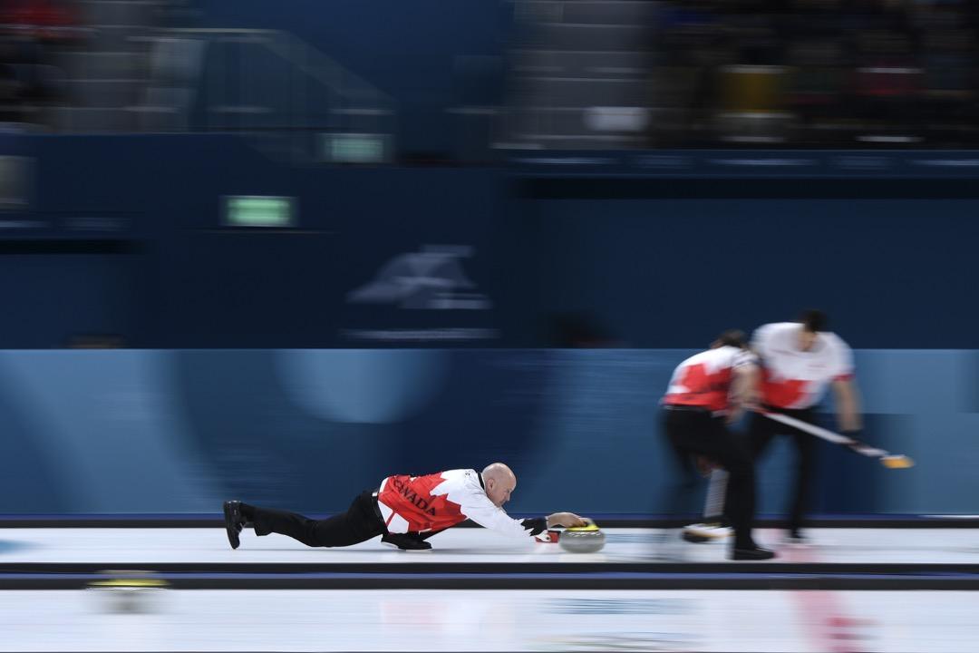 2018年2月21日,在加拿大對丹麥的冰壺比賽循環賽階段中,加拿大隊的 Kevin Koe 把冰壺推向賽道另一端的標靶。