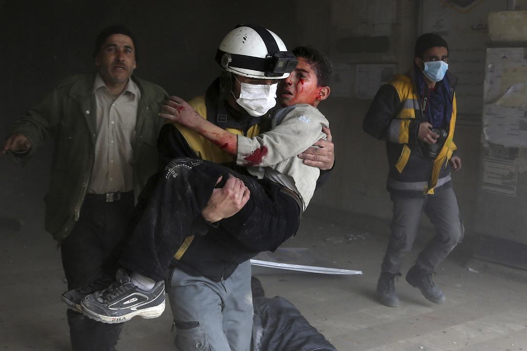 敘利亞政府軍對烏塔大馬士革(Ghouta Damascus)的反對派據點連續第四天發動空襲。圖為2月8日,一名民間救援組織「民間防衞隊」(俗稱:白頭盔,White Helmets)成員救出一名在政府軍空襲中受傷的兒童。 攝:Abdulmonam Eassa / Getty Images