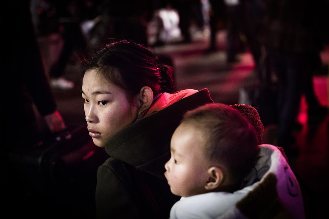 廣州車站外,一對母子等待進入火車站。