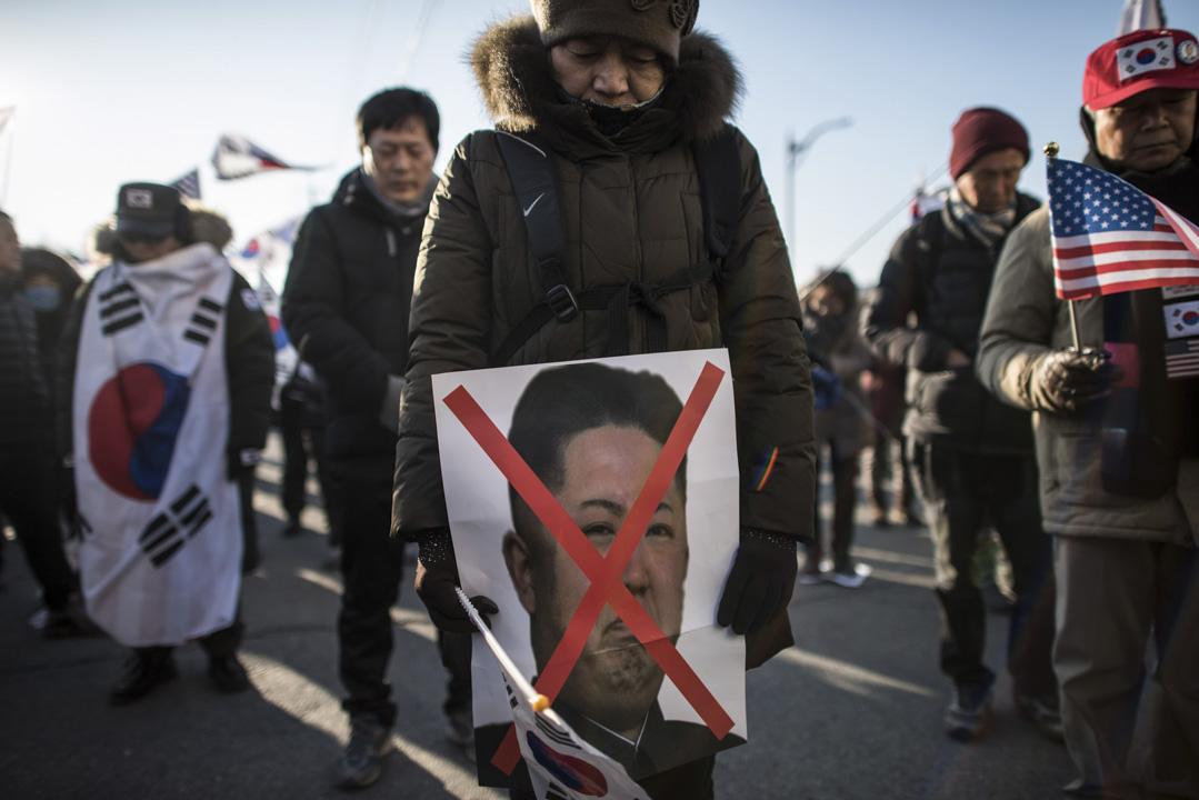 2018年2月6日,南韓平昌冬季奧運會即將開幕,北韓三池淵管弦樂團一行百餘人入境南韓,停泊在東海市墨湖港,準備冬奧表演。數以百計南韓民眾則在碼頭附近憤怒示威,有示威者拿着畫上大交叉的金正恩肖像圖,抗議北韓參加冬奧會。
