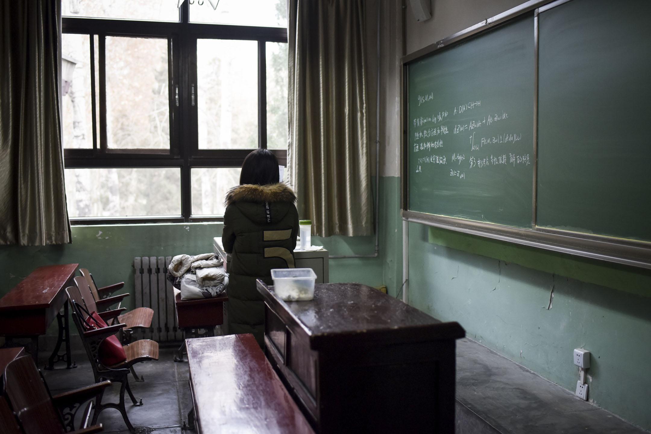 北京航空航天大學畢業生羅茜茜實名舉報教授陳小武性騷擾。翌日,女權主義者張累累發起「萬人致信母校」行動,呼籲高校畢業生或在讀學生向母校發出公開信——要求大學建立反性騷擾機制。圖為2018年1月17日,北京航空航天大學一名女學生在一個教室裏。 攝:Wang Zhao/AFP/Getty Images