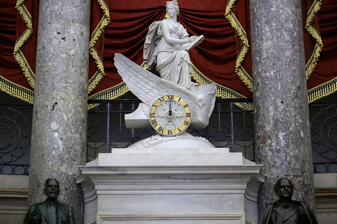隨着美國國會山莊 Chariot 雕像大鐘的指針指向當地週四(8日)午夜,美國聯邦政府陷入今年內的第二次停擺。 攝:Chip Somodevilla / Getty Images