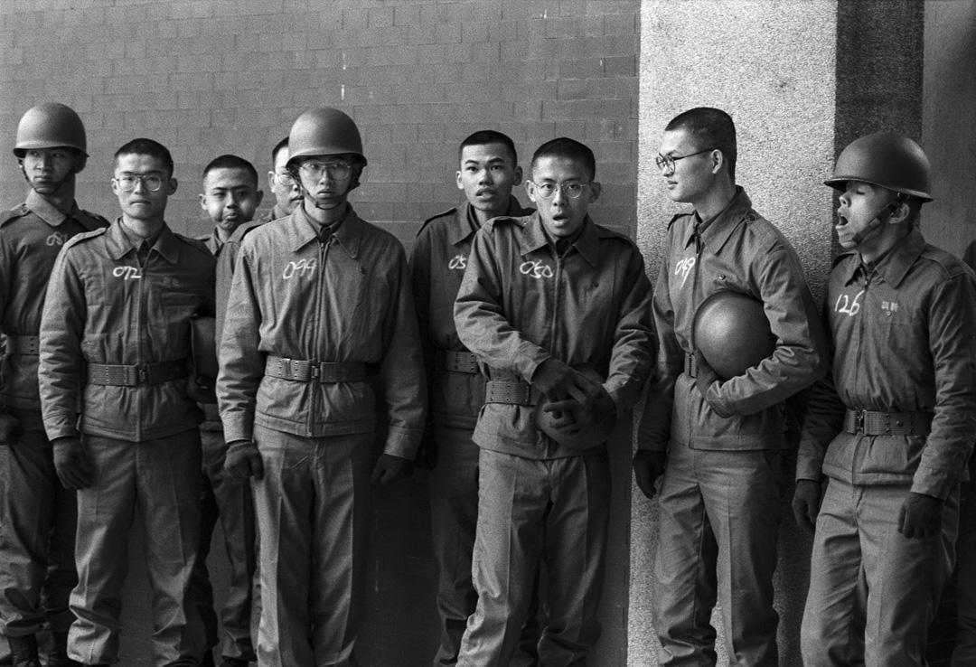 一群剛報到幾天,排隊等待拍攝大頭照的大專集訓學生,衣服上用粉筆寫着學號,個個表情是菜鳥,面對軍中環境的茫然。