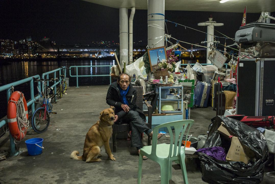 年近65嵗的興叔,已在觀塘碼頭住了一年半,身邊陪伴他的是他契女所養的唐狗。雖然他的家看似只是一堆雜物,但對興叔來説是他的安樂窩。 攝:林振東/端傳媒