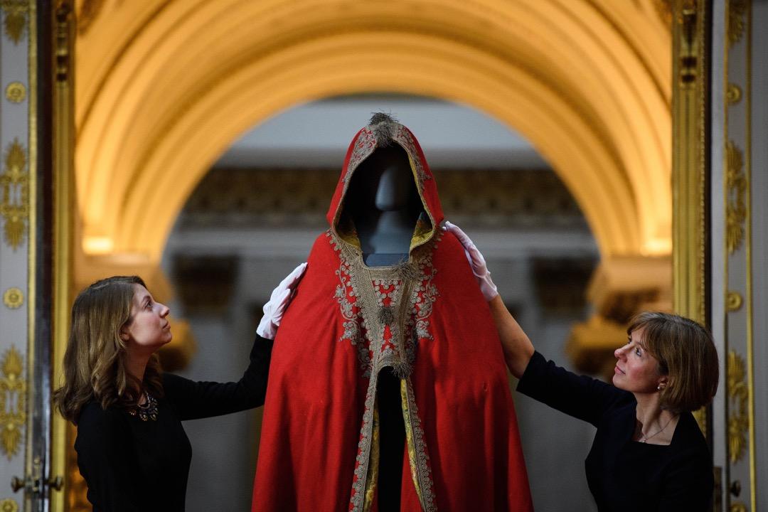 2018年3月28日,英國王儲查理斯70大壽前夕,皇家收藏信託 (Royal Collection Trust) 的工作人員為慶祝查理斯王子生日的展覽預備展品,其中包括拿破崙的斗篷。