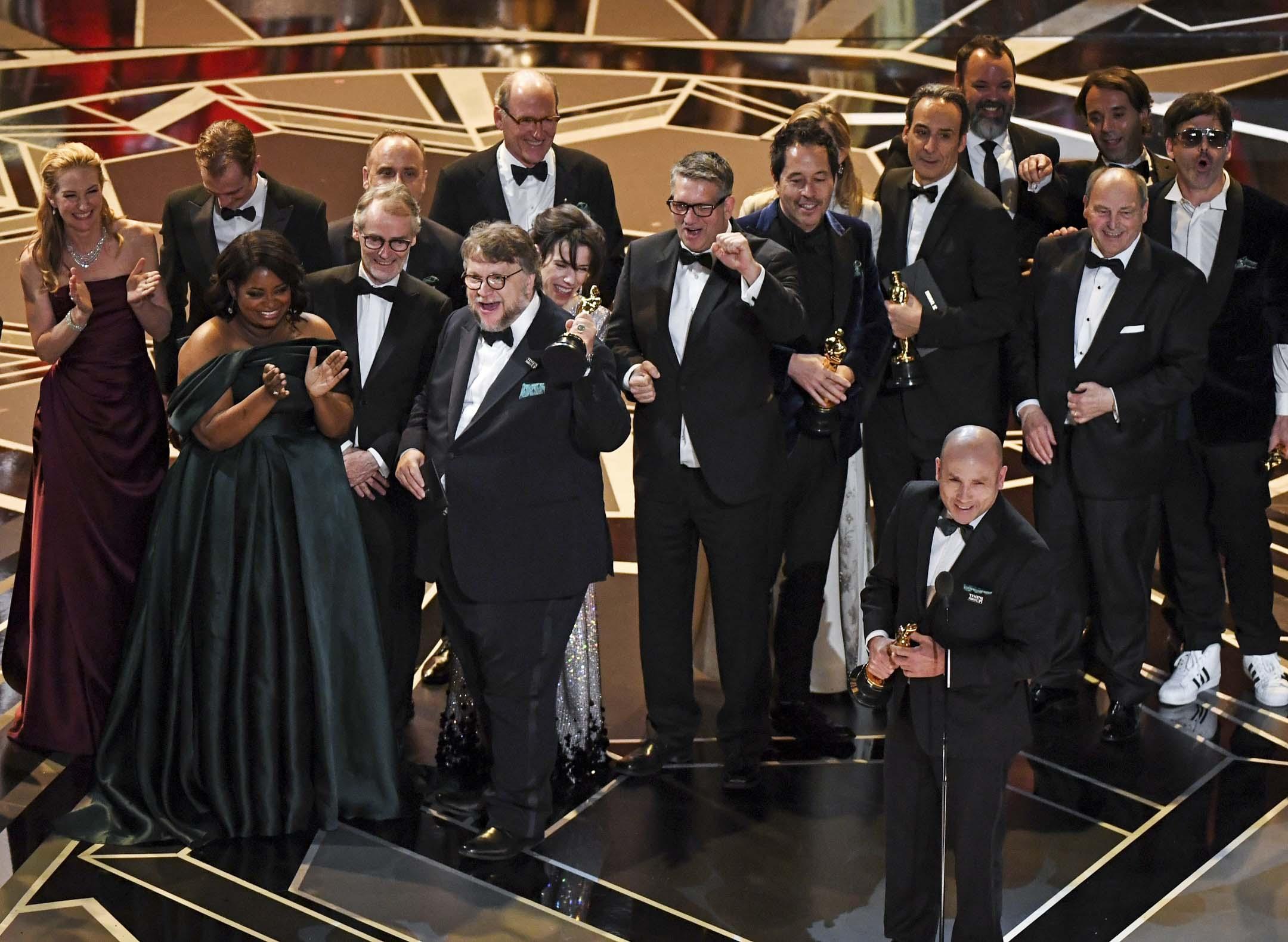 《忘形水》(The Shape of Water)獲得最佳影片,一眾創作者上台領獎。有十三項提名的《 忘形水 》,贏得最佳電影、最佳導演、最佳原創音樂和最佳製作設計四個獎項。 攝: Mark Ralston/AFP/Getty Images